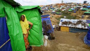 En flyktingkvinna står utanför ett skjul byggt av trä och presenningar i flyktinglägret för Rohingyer i Cox's Bazar i Bangladesh.