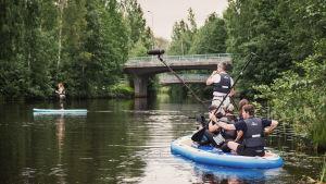 Ett filmteam trängs på en SUP-bräda medan de filmar redaktören Hannamari Hoikkala som står och paddlar på en annan SUP-bräda.