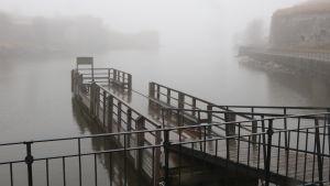 En brygga ut i dimmigt vatten vid Sveaborg.