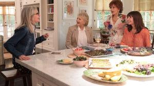 Fyra väninnor i ivrigt samspråk över en bit mat.