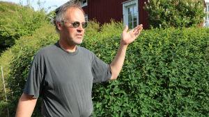 Kjell Wickman vid en grönskande häck av Blåtry