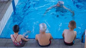 Tre barn och en simlärare i en simbassäng.
