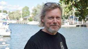 En man står i svart t-skjorta och ler mot kameran. I bakgrunden syns en hamn med vatten och båtar. Även träd syns i bakgrunden.