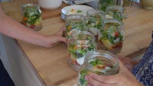 händer som tar burkar med grönsaker