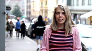 Leende blond kvinna i halvbild , iklädd randig tröja och rosa kofta.