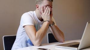 En ung man i vit t-shirt sitter vid en dator med ansiktet i händerna.
