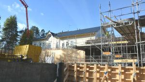 En byggarbetsplats med olika träkonstruktioner. Bakom står ett gult trähus.