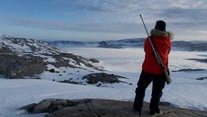 En person iklädd vinterkläder med pälskantad huva. Har ett gevär på ryggen. Står på ett berg och tittar ut över ett snölandskap. Befinner sig på Grönland.