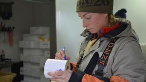 Marie Kellgren ser koncentrerad ut medan hon skriver på en vit pappersrulle.