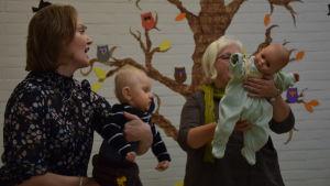 Två kvinnor står med barn respektive docka i famnen. De sjunger och vaggar eller gungar med barnet/dockan. Musiklek