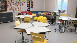 Bord och stolar i ett klassrum. I bakgrunden syns en soffa. På väggen är flera papegojor gjorda av papper upphängda.