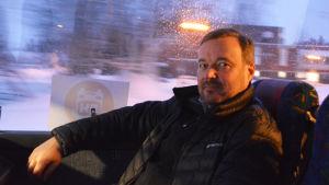 En medelålders man sitter i en buss. Bakom honom synns ett mörkt och snöigt landskap.