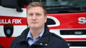 Jens Tegengren står framför en brandbil och tittar rakt in i kameran med en allvarlig min.