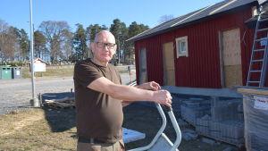 En man med skottkärra vid ett bygge. Bakom ett halvfärdig byggnad med väggar målade i rödmylla.