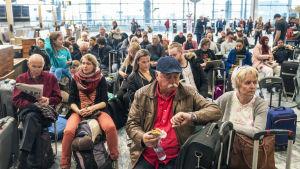 Resenärer sitter och väntar på en flygplats och en man tittar på klockan.
