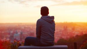 En pojke sitter med ryggen mot uppe på en kulle och tittar ut mot en stad.
