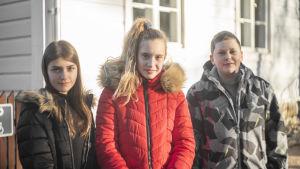 Tre barn står framför ett vitt trähus. De ler och ser in i kameran.