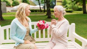en ung kvinna räcker en blombukett till en äldre dam, båda sitter på en parkbänk.