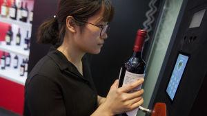 En kvinna testar företaget Alibabas ansiktsigenkänningssystem för köp av alkohol på vinmässan VinExpo i Hongkong våren 2018.