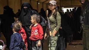 SDF-milis står vakt medan kvinnor och barn förbereder sig på att stiga ombord på bussar som ska föra dem ut ur lägert al-Hol i nordöstra Syrien 3.6.2019.