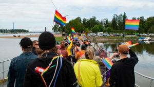 En Prideparad på en bro ut till en ö.