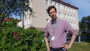 Raseborgs miljöinspektör Aapo Ahola framför stadshuset bredvid en vresrosbuske.