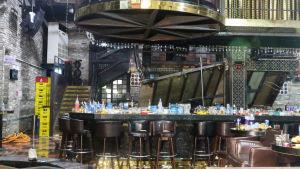En tom nattklubb där tomma flaskor står kvar på ett bord