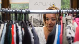 Kuvassa Heidi Jaari selaa Apuna ry:lle tulleita vaatteita