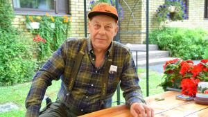 En man sittandes vid ett bord utomhus.