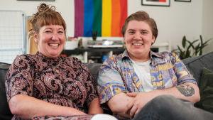 en mamma och hennes som som är trans sitter på en soffa och ler brett till kameran