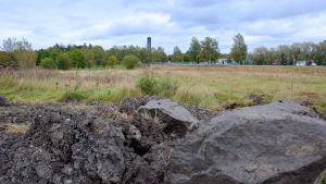 stenar och gräs på ängen som ska grävas upp för nya handelskajen, i bakgrunden syns en k-marketskylt