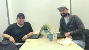 två män sitter i en kafeteria med keps på sig och varsin laptop framför sig