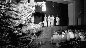 En svartvit bild på lågstadiebarn utklädda till stjärngossar som står på en scen på skolans julfest. Barn sitter i publiken och tittar på.
