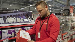 Raision Verkkokauppa.comin myynnin työnjohtaja Jani Heikkilä pitelee käsissään itkuhälytintä.