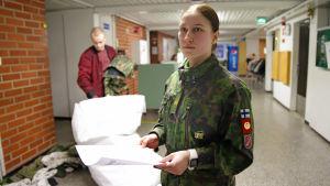 Alikersantti Emilia Jaakkola tekee varustarkastusta uusille alokkaille Parolannummella.