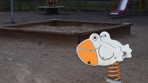 En gunga för barn som föreställer en anka eller pelikan i en lekpark. Sandlåda och rutschbana i bakgrunden. Inga barn.