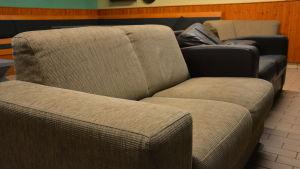En ljusgrå och svart soffa i en föreningslokal.