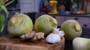 Rotfrukter och lök på en skärbrada i ett kök