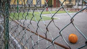 En orange boll på en asfalterad fotbollsplan omgiven av ett staket