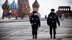 Två poliser patrullerar på ett näst intill tomt Röda torget i Moskva.