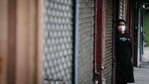 En kvinna i mask väntar på kunder till sitt snabbkök i New York.