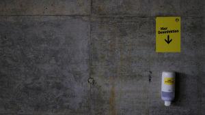 """En svart vägg och en desinfektionsflaska fäst på väggen och ovanför en guldfärgad skylt med en pil mot flaskan där det på tyska står """"Här desinfektion""""."""
