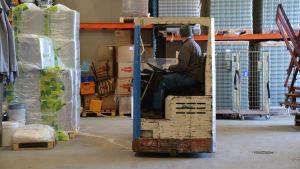 Tomas Bruce sitter i sin truck och kör inne i en stor industrihall.