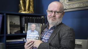 Jari Lindström visar upp pärmbilden på sin memoarbok