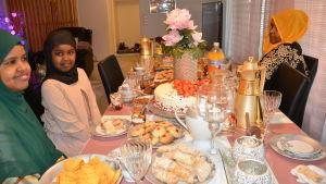 Festmiddag vid dukat bord, några kvinnor i slöja.
