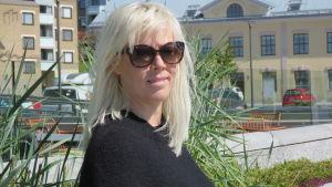 En kvinna med långt blont hår, svart tröja och solglasögon står ute på en uteservering. Hus och parkerade bilar i bakgrunden.