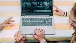 Tietokone, jonka näytöltä näkyy Yle Areenan ohjelmasivu. Oikeassa reunassa naurava nainen, joka katsoo tietokoneen käyttäjään. Tietokoneen käyttäjästä näkyvät vain kädet.