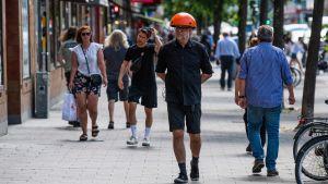 """En man med en """"coronahatt"""" som signalerar avstånd. Larmet går om någon eller något kommer på mindre än 1,5 meters avstånd."""
