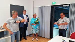 Tre glada män och en kvinna med en blombukett står i ett kontorsrum. Mannen till vänster gör en coronahälsning med armbågen.