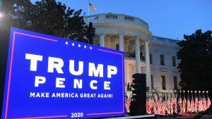 """Plakat där det står """"Trump Pence"""". Vita huset och USA:s flaggor i bakgrunden."""